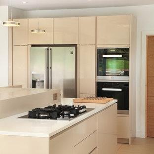Diseño de cocina comedor en U, minimalista, grande, con suelo de baldosas de porcelana, armarios con paneles lisos, puertas de armario beige y una isla
