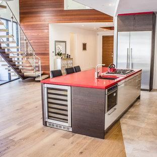 Imagen de cocina comedor lineal, contemporánea, de tamaño medio, con fregadero bajoencimera, armarios con paneles lisos, puertas de armario de madera en tonos medios, encimera de acrílico, salpicadero blanco, electrodomésticos de acero inoxidable, suelo de madera clara, una isla, suelo marrón y encimeras rojas
