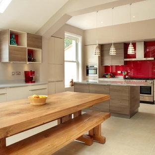 Offene, Große Moderne Küche in U-Form mit flächenbündigen Schrankfronten, beigen Schränken, Küchenrückwand in Rot, Küchengeräten aus Edelstahl, Kücheninsel, Quarzit-Arbeitsplatte und Glasrückwand in Buckinghamshire
