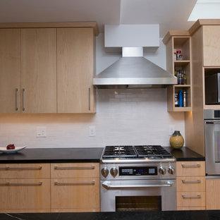 Idéer för att renovera ett stort funkis svart svart kök, med en undermonterad diskho, släta luckor, bänkskiva i täljsten, vitt stänkskydd, rostfria vitvaror, en köksö, skåp i ljust trä, stänkskydd i keramik, mellanmörkt trägolv och orange golv
