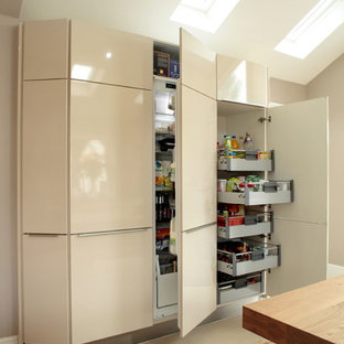 Inspiration for a contemporary kitchen/diner in Buckinghamshire with flat-panel cabinets, beige cabinets and beige floors.