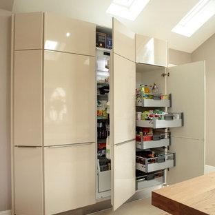 Moderne Wohnküche mit flächenbündigen Schrankfronten, beigen Schränken und beigem Boden in Buckinghamshire