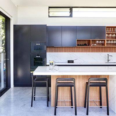 Eat-in kitchen - large contemporary single-wall gray floor and concrete floor eat-in kitchen idea in Sydney with an undermount sink, white backsplash, black appliances, an island, black cabinets, quartz countertops, stone slab backsplash and white countertops
