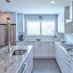 Mittelgroße Moderne Wohnküche in L-Form mit Unterbauwaschbecken, flächenbündigen Schrankfronten, gelben Schränken, Granit-Arbeitsplatte, Küchenrückwand in Weiß, Rückwand aus Metrofliesen, Küchengeräten aus Edelstahl, Travertin und Kücheninsel in Philadelphia