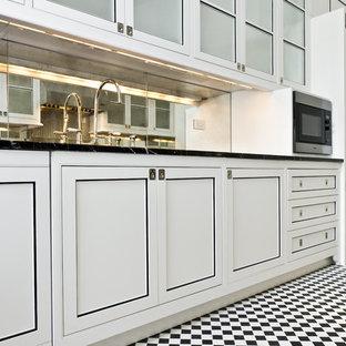 Diseño de cocina de galera, actual, pequeña, cerrada, sin isla, con fregadero bajoencimera, armarios con paneles lisos, puertas de armario blancas, encimera de granito, salpicadero con efecto espejo, electrodomésticos de acero inoxidable y suelo de baldosas de cerámica