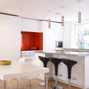Cette photo montre une grande cuisine américaine tendance avec un îlot central, un placard à porte plane, des portes de placard blanches, un plan de travail en surface solide, une crédence orange, une crédence en carreau de verre et un électroménager blanc.