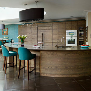 Inspiration for a huge contemporary open concept kitchen remodel in London with flat-panel cabinets, dark wood cabinets, paneled appliances, an island and solid surface countertops