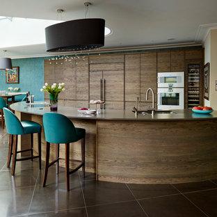 ロンドンの巨大なコンテンポラリースタイルのおしゃれなキッチン (フラットパネル扉のキャビネット、濃色木目調キャビネット、パネルと同色の調理設備、人工大理石カウンター) の写真