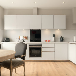 Example of a trendy l-shaped light wood floor eat-in kitchen design in Edinburgh with an undermount sink, flat-panel cabinets, white cabinets, black backsplash, stainless steel appliances and no island