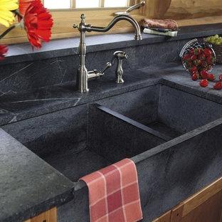 他の地域の中サイズのトランジショナルスタイルのおしゃれなキッチン (エプロンフロントシンク、シェーカースタイル扉のキャビネット、中間色木目調キャビネット、ソープストーンカウンター、ベージュキッチンパネル、木材のキッチンパネル、シルバーの調理設備の、セラミックタイルの床、アイランドなし、ベージュの床) の写真