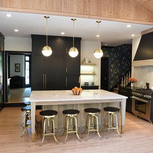 Cette image montre une grande cuisine design en U avec un évier encastré, un placard à porte shaker, des portes de placard noires, un plan de travail en quartz modifié, une crédence blanche, une crédence en dalle de pierre, un électroménager encastrable, un sol en bois clair, un îlot central et un sol beige.
