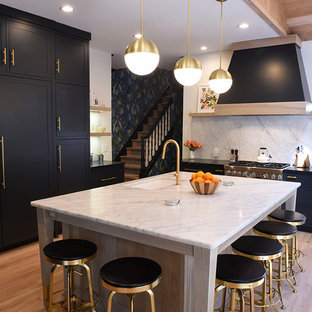 Large contemporary kitchen in Cleveland with a submerged sink, shaker cabinets, black cabinets, white splashback, an island, engineered stone countertops, stone slab splashback, integrated appliances, light hardwood flooring and beige floors.