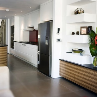 Inspiration for a mid-sized contemporary single-wall open plan kitchen in London with an undermount sink, flat-panel cabinets, white cabinets, glass benchtops, grey splashback, glass sheet splashback, stainless steel appliances, ceramic floors and with island.