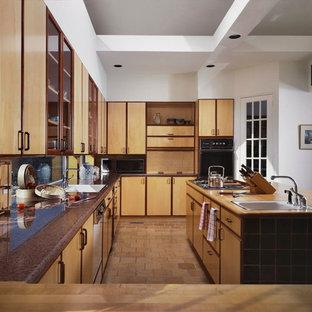 ニューヨークの大きいコンテンポラリースタイルのおしゃれなキッチン (ドロップインシンク、フラットパネル扉のキャビネット、淡色木目調キャビネット、御影石カウンター、ガラスタイルのキッチンパネル、黒い調理設備、テラコッタタイルの床、茶色い床) の写真