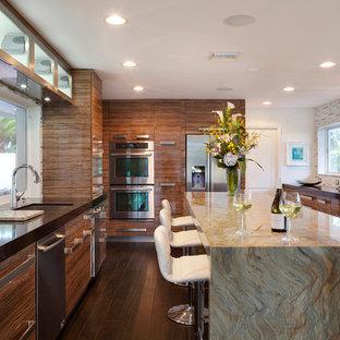 Inspiration för ett avskilt, mycket stort funkis svart svart parallellkök, med en undermonterad diskho, släta luckor, skåp i mellenmörkt trä, flerfärgad stänkskydd, stänkskydd i stickkakel, rostfria vitvaror, mörkt trägolv, en köksö och brunt golv