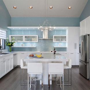 Geschlossene, Geräumige Moderne Küche in L-Form mit Unterbauwaschbecken, Glasfronten, weißen Schränken, Küchenrückwand in Blau, Küchengeräten aus Edelstahl, dunklem Holzboden, Kücheninsel, Granit-Arbeitsplatte, Rückwand aus Glasfliesen, braunem Boden und weißer Arbeitsplatte in Miami