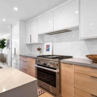 This is an example of a large contemporary l-shaped open plan kitchen in Los Angeles with an integrated sink, flat-panel cabinets, white cabinets, quartz benchtops, white splashback, marble splashback, stainless steel appliances, light hardwood floors, with island, beige floor and grey benchtop.