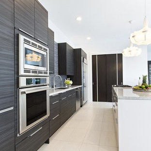 Large contemporary single-wall kitchen in Houston with flat-panel cabinets, black cabinets, grey splashback, stainless steel appliances, with island, an undermount sink, porcelain floors, white floor, quartzite benchtops and stone tile splashback.