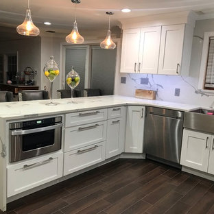 Design ideas for a medium sized contemporary u-shaped kitchen/diner in Boston with a belfast sink, shaker cabinets, white cabinets, engineered stone countertops, multi-coloured splashback, stone slab splashback, stainless steel appliances, dark hardwood flooring, a breakfast bar, brown floors and multicoloured worktops.