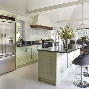 This is an example of a medium sized traditional single-wall kitchen/diner in Surrey with a submerged sink, shaker cabinets, green cabinets, granite worktops, black splashback, glass sheet splashback, stainless steel appliances and an island.