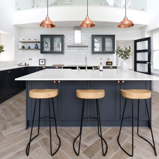 Photo of a large classic l-shaped kitchen in Essex with a submerged sink, shaker cabinets, black cabinets, composite countertops, white splashback, ceramic splashback, integrated appliances, light hardwood flooring, an island, beige floors and white worktops.