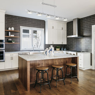 Farmhouse kitchen ideas - Example of a farmhouse l-shaped medium tone wood floor and brown floor kitchen design in Los Angeles with a farmhouse sink, shaker cabinets, white cabinets, gray backsplash, stainless steel appliances, an island and gray countertops