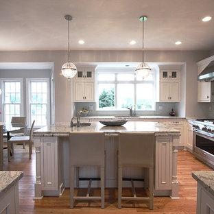 Ejemplo de cocina comedor en L, clásica, con armarios con paneles empotrados, puertas de armario blancas, salpicadero verde y electrodomésticos de acero inoxidable