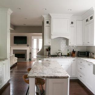 Imagen de cocina clásica, cerrada, con electrodomésticos de acero inoxidable, salpicadero de azulejos tipo metro, fregadero sobremueble, armarios con paneles empotrados, puertas de armario blancas, encimera de granito y salpicadero blanco