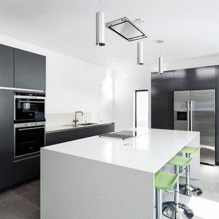 Medium sized contemporary u-shaped open plan kitchen in Hampshire with a double-bowl sink, flat-panel cabinets, brown cabinets, composite countertops, grey splashback, glass sheet splashback, stainless steel appliances, porcelain flooring and an island.