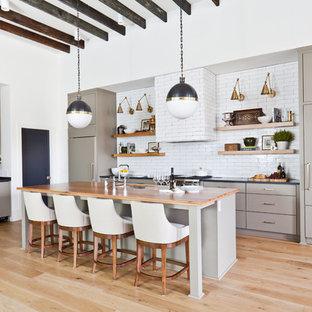 Inspiration för ett mellanstort funkis orange linjärt oranget kök med öppen planlösning, med en undermonterad diskho, släta luckor, gröna skåp, träbänkskiva, vitt stänkskydd, stänkskydd i keramik, rostfria vitvaror, ljust trägolv och en köksö