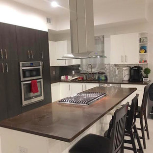Photo of a contemporary l-shaped kitchen in New York with flat-panel cabinets, white cabinets, concrete benchtops, grey splashback, subway tile splashback, stainless steel appliances, marble floors and with island.