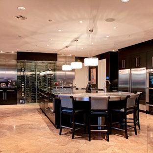 フェニックスの大きいコンテンポラリースタイルのおしゃれなキッチン (ドロップインシンク、フラットパネル扉のキャビネット、黒いキャビネット、人工大理石カウンター、ベージュキッチンパネル、セラミックタイルの床、シルバーの調理設備の、ベージュの床) の写真