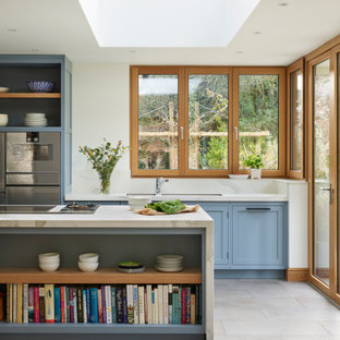 Inspiration for a large classic galley kitchen in Berkshire with a submerged sink, shaker cabinets, blue cabinets, stainless steel appliances, porcelain flooring, an island, grey floors and white worktops.