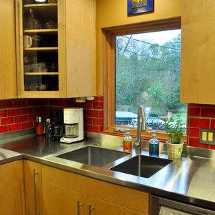 ダラスの小さいコンテンポラリースタイルのおしゃれなキッチン (一体型シンク、フラットパネル扉のキャビネット、淡色木目調キャビネット、ステンレスカウンター、赤いキッチンパネル、セラミックタイルのキッチンパネル、シルバーの調理設備の、コルクフローリング) の写真