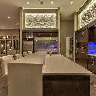 Bild på ett mycket stort, avskilt funkis u-kök, med släta luckor, skåp i mörkt trä, bänkskiva i kvartsit, vitt stänkskydd, stänkskydd i sten, rostfria vitvaror, en köksö, en undermonterad diskho och brunt golv