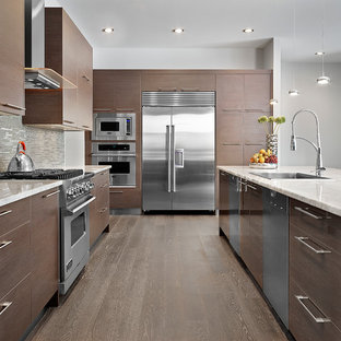 Contemporary l-shaped kitchen in Edmonton with a drop-in sink, flat-panel cabinets, dark wood cabinets, grey splashback, matchstick tile splashback and stainless steel appliances.