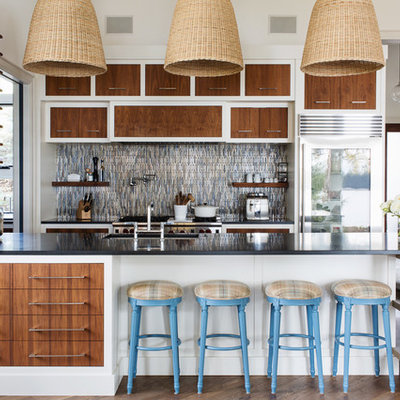 Large trendy galley medium tone wood floor and brown floor open concept kitchen photo in Toronto with an undermount sink, flat-panel cabinets, medium tone wood cabinets, granite countertops, multicolored backsplash, ceramic backsplash, stainless steel appliances and a peninsula