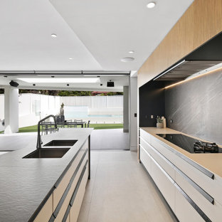 This is an example of a large contemporary galley eat-in kitchen in Sydney with a double-bowl sink, flat-panel cabinets, white cabinets, black splashback, porcelain splashback, stainless steel appliances, porcelain floors, with island, grey floor and white benchtop.