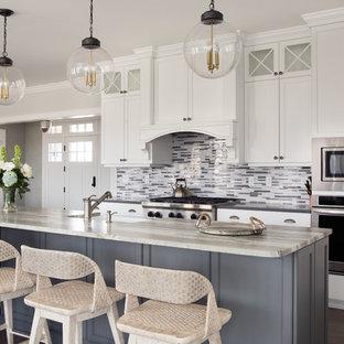 ニューヨークの広いビーチスタイルのおしゃれなキッチン (エプロンフロントシンク、インセット扉のキャビネット、白いキャビネット、グレーのキッチンパネル、ボーダータイルのキッチンパネル、シルバーの調理設備、濃色無垢フローリング、茶色い床) の写真