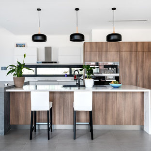 Design ideas for a contemporary kitchen in Perth with a drop-in sink, flat-panel cabinets, medium wood cabinets, black appliances, multiple islands, grey floor and white benchtop.