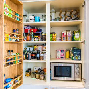 This is an example of a large contemporary galley kitchen pantry in Other with an integrated sink, shaker cabinets, grey cabinets, wood worktops, white splashback, ceramic splashback, integrated appliances, medium hardwood flooring, a breakfast bar and brown floors.