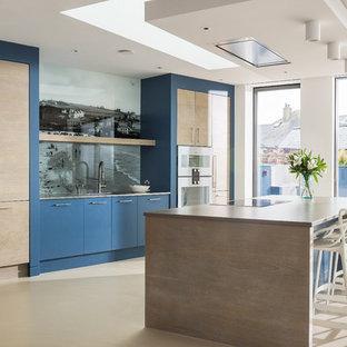 コーンウォールの大きいコンテンポラリースタイルのおしゃれなキッチン (フラットパネル扉のキャビネット、珪岩カウンター、マルチカラーのキッチンパネル、ガラス板のキッチンパネル、パネルと同色の調理設備、コンクリートの床、ベージュの床、ベージュのキッチンカウンター、青いキャビネット) の写真