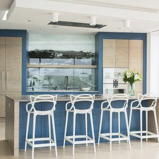 コーンウォールの大きいコンテンポラリースタイルのおしゃれなキッチン (ドロップインシンク、フラットパネル扉のキャビネット、中間色木目調キャビネット、珪岩カウンター、マルチカラーのキッチンパネル、ガラス板のキッチンパネル、パネルと同色の調理設備、コンクリートの床、ベージュの床、ベージュのキッチンカウンター) の写真