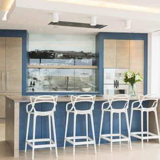 Inspiration for a large contemporary single-wall open plan kitchen in Cornwall with a drop-in sink, flat-panel cabinets, medium wood cabinets, quartzite benchtops, multi-coloured splashback, glass sheet splashback, panelled appliances, concrete floors, with island, beige floor and beige benchtop.