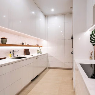 Huge contemporary kitchen pantry designs - Example of a huge trendy galley beige floor kitchen pantry design in Orange County with flat-panel cabinets, marble countertops, white backsplash, stone slab backsplash, an undermount sink, white cabinets and white countertops