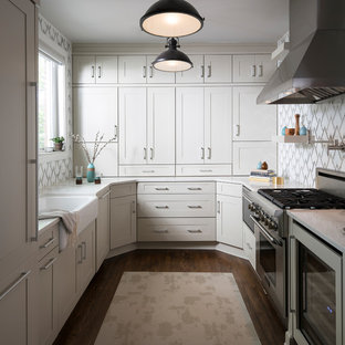 Large contemporary eat-in kitchen designs - Large trendy u-shaped dark wood floor and brown floor eat-in kitchen photo in New York with a farmhouse sink, shaker cabinets, gray cabinets, quartz countertops, multicolored backsplash, mirror backsplash, stainless steel appliances and a peninsula