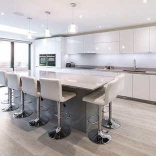 Inspiration for an expansive modern single-wall open plan kitchen in London with flat-panel cabinets, grey cabinets, quartz worktops, white splashback, glass sheet splashback, black appliances, an island, grey worktops, a submerged sink, light hardwood flooring and beige floors.