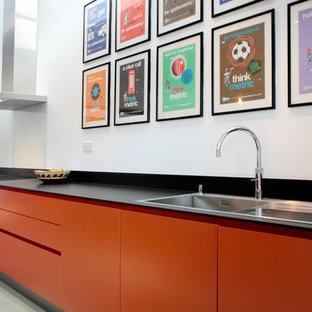 Offene, Zweizeilige, Große Moderne Küche mit flächenbündigen Schrankfronten, orangefarbenen Schränken, Küchenrückwand in Blau, Glasrückwand, Küchengeräten aus Edelstahl, Einbauwaschbecken, Quarzit-Arbeitsplatte, dunklem Holzboden und Kücheninsel in Hertfordshire