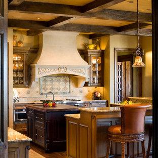 ウィチタの中サイズの地中海スタイルのおしゃれなキッチン (アンダーカウンターシンク、インセット扉のキャビネット、ベージュのキャビネット、タイルカウンター、ベージュキッチンパネル、磁器タイルのキッチンパネル、シルバーの調理設備の、無垢フローリング) の写真