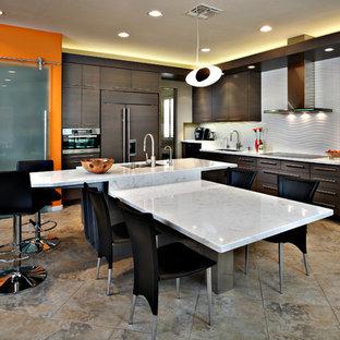 フェニックスの広いコンテンポラリースタイルのおしゃれなキッチン (フラットパネル扉のキャビネット、濃色木目調キャビネット、白いキッチンパネル、パネルと同色の調理設備、アンダーカウンターシンク、セラミックタイルの床、茶色い床) の写真